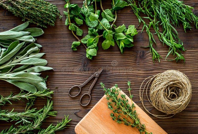 La configuration plate avec les herbes et la verdure fraîches pour sécher et faire des épices a placé sur le fond en bois de cuis images stock