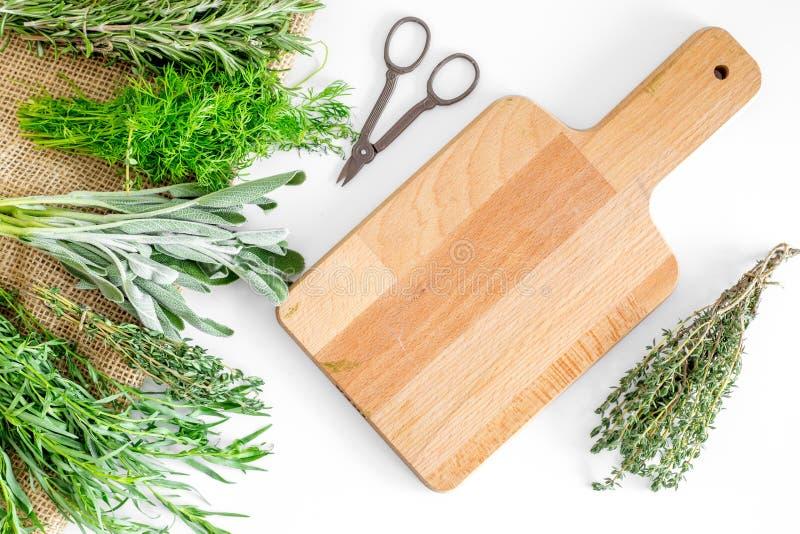 La configuration plate avec les herbes et la verdure fraîches pour sécher et faire des épices a placé sur la maquette blanche de  images stock