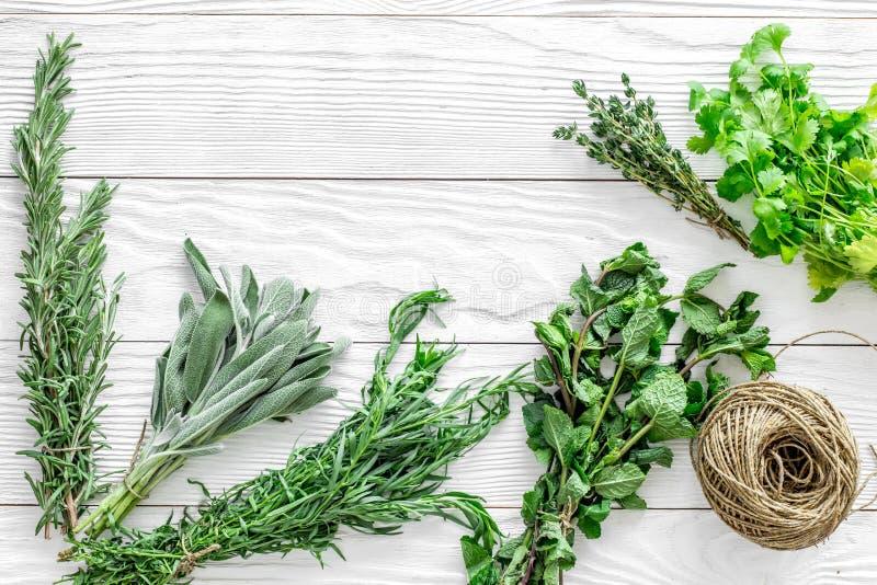 La configuration plate avec les herbes et la verdure fraîches pour sécher et faire des épices a placé sur la maquette en bois bla photo stock