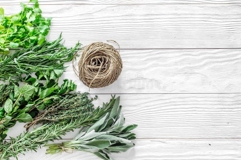 La configuration plate avec les herbes et la verdure fraîches pour sécher et faire des épices a placé sur la maquette en bois bla images stock