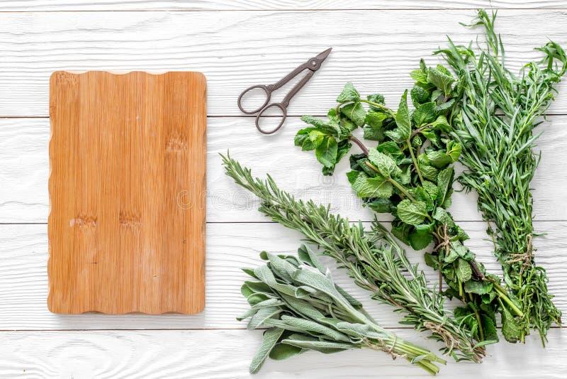 La configuration plate avec les herbes et la verdure fraîches pour sécher et faire des épices a placé sur la maquette en bois bla photographie stock libre de droits