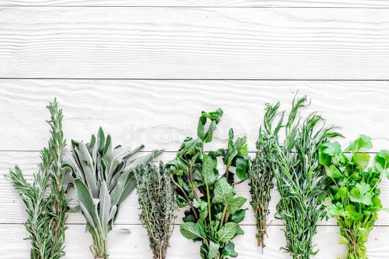 La configuration plate avec les herbes et la verdure fraîches pour sécher et faire des épices a placé sur la maquette en bois bla image stock