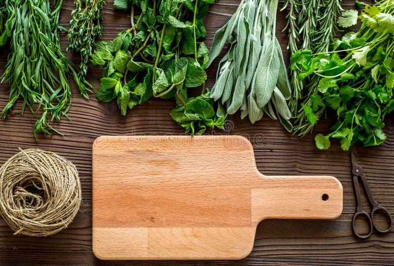 La configuration plate avec les herbes et la verdure fraîches pour sécher et faire des épices a placé sur la maquette en bois de  photographie stock libre de droits