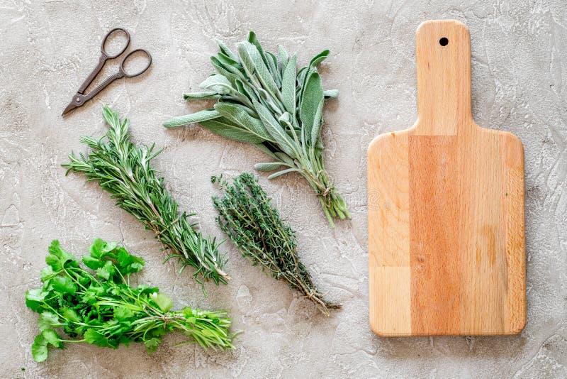 La configuration plate avec les herbes et la verdure fraîches pour sécher et faire des épices a placé sur la maquette en pierre d photo stock