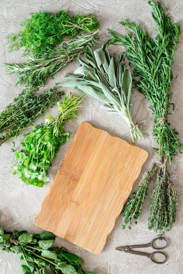 La configuration plate avec les herbes et la verdure fraîches pour sécher et faire des épices a placé sur la maquette en pierre d photos stock