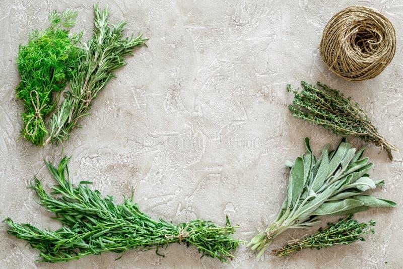 La configuration plate avec les herbes et la verdure fraîches pour sécher et faire des épices a placé sur la maquette en pierre d photos libres de droits