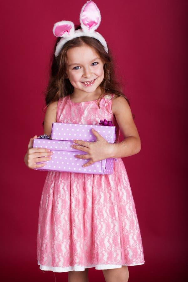 La coniglietta felice sta tenendo i contenitori di regalo fotografia stock