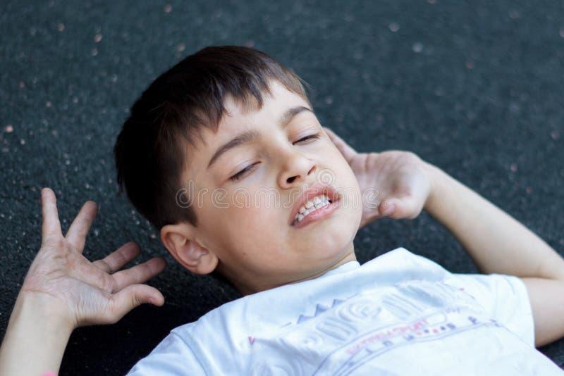 la conmoción cerebral del dolor de cabeza, un pequeño niño bajó y golpeó su cabeza en el asfalto, muy doloroso foto de archivo libre de regalías
