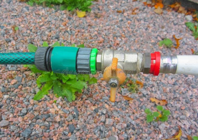 La connexion de la conduite d'eau et un tuyau d'arrosage avec une valve recouvrent images stock