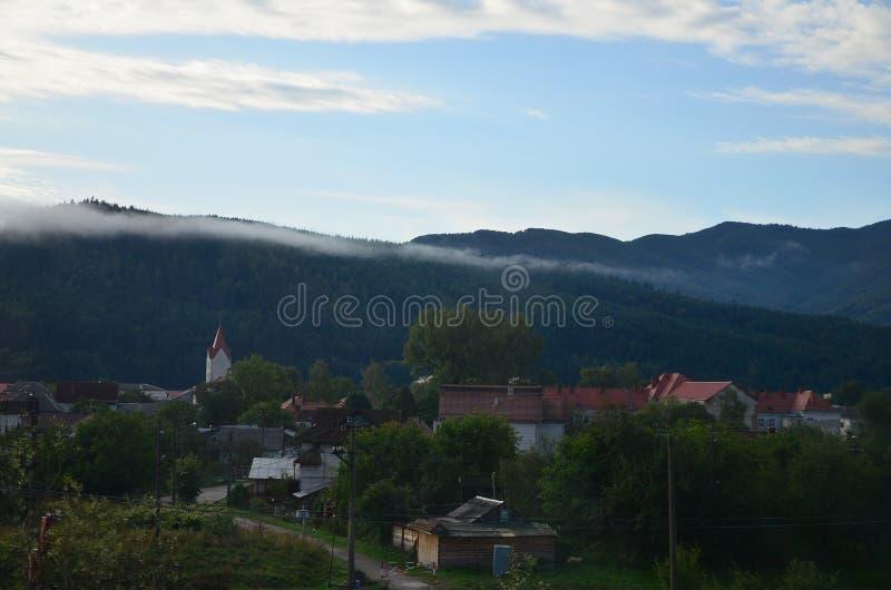 La construcción de viviendas está delante de una capa gruesa de niebla Viviendo en un área montañosa en los Cárpatos, Ucrania imagen de archivo libre de regalías