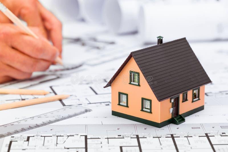 La construcción planea con las herramientas de dibujo y la miniatura de la casa en azul imagenes de archivo