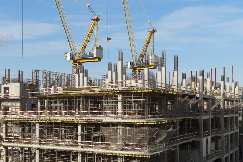 La construction d'un bâtiment sur plusieurs étages. Deux grues de construction sur un bâtiment. Scaffolage sur plusieurs image libre de droits
