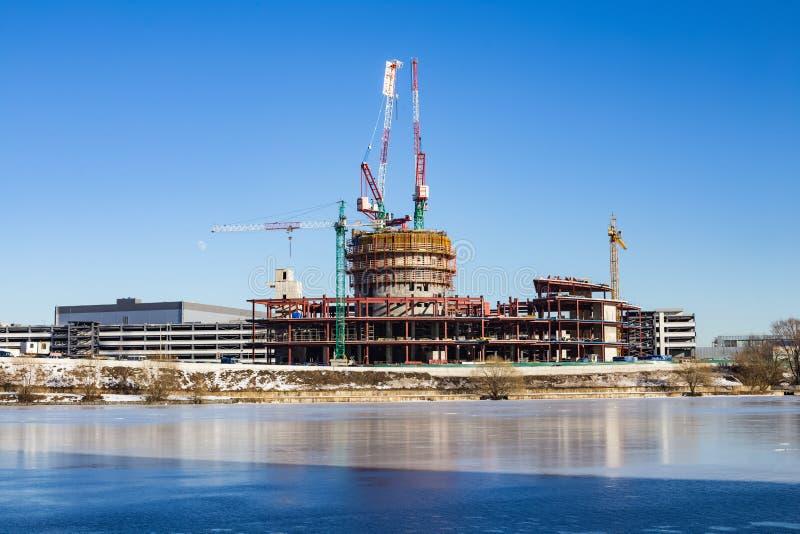 La construction des bâtiments en hiver sur la rivière congelée images libres de droits