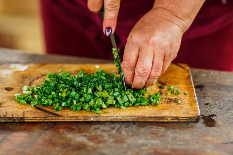 La consumición sana, cocinero de sexo femenino corta la cebolla verde fresca para la ensalada imagen de archivo