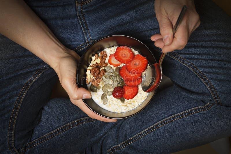 La consumición sana, cuenco del desayuno, yogur, granola, semillas, frutas frescas, cuenco, mano del ` s de la mujer, limpia la c foto de archivo