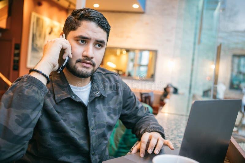 La conversación telefónica concentró al hombre serio que trabajaba en café usando el teléfono y el ordenador portátil Forma de vi fotos de archivo