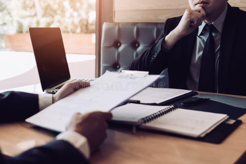 La conversazione importante dell'uomo d'affari asiatico serio con l'impiegato maschio sta esaminando i documenti del riassunto fotografie stock