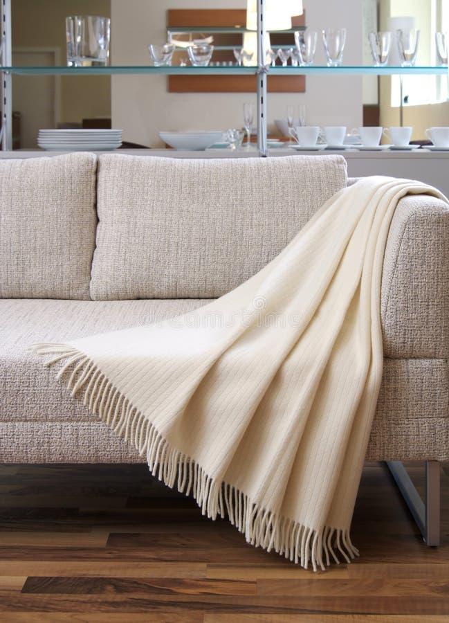 La coperta ha coperto sopra un divano immagine stock