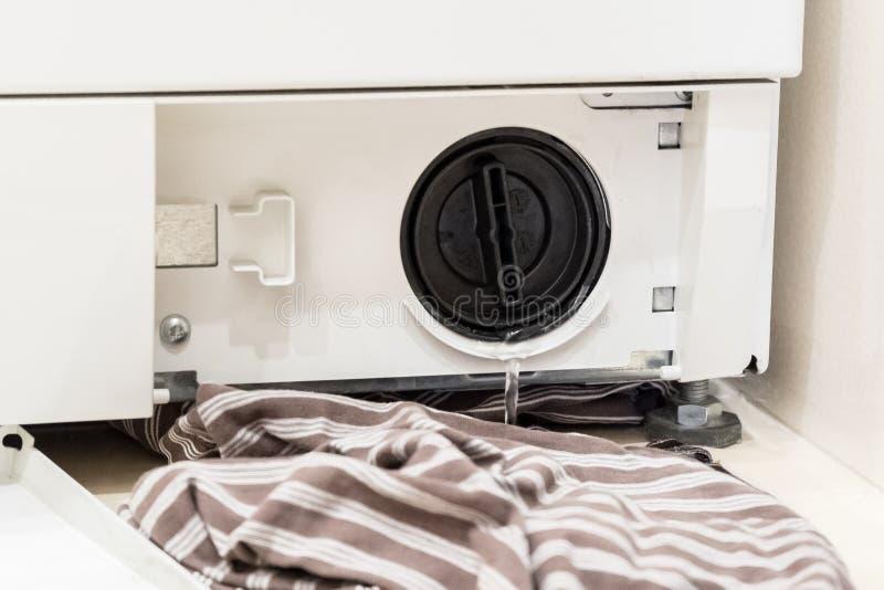 La copertura aperta del filtrante della lavatrice sta versando l'acqua immagini stock