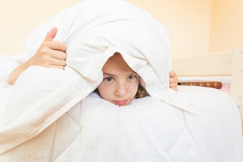 La copertura infastidita della ragazza con il cuscino e non vuole alzarsi fotografie stock