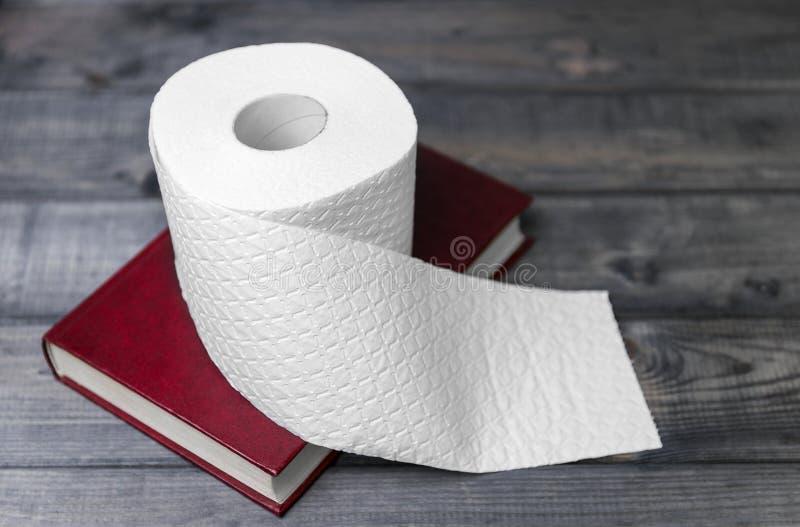 La copertura rossa della copertina dura da indicare ed il bianco hanno impresso il rotolo di PA della toilette fotografie stock