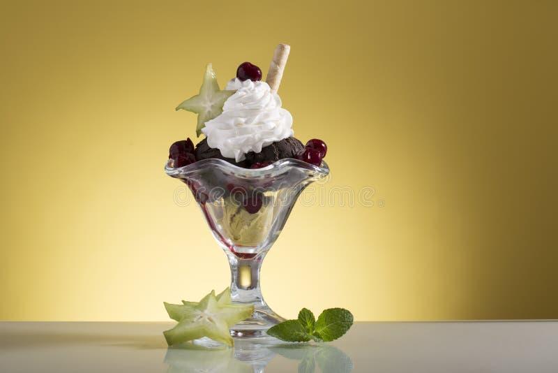 La coppa gelato variopinta della ciliegia con crema wipping e la carambola decorano fotografia stock