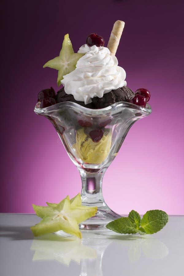 La coppa gelato variopinta della ciliegia con crema wipping e la carambola decorano immagini stock
