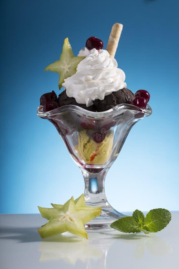 La coppa gelato variopinta della ciliegia con crema wipping e la carambola decorano immagine stock libera da diritti