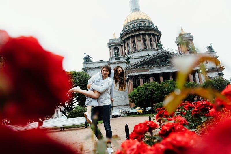 La coppia amorosa abbraccia contro un fondo dei fiori rossi e dell'architettura d'annata fotografie stock libere da diritti