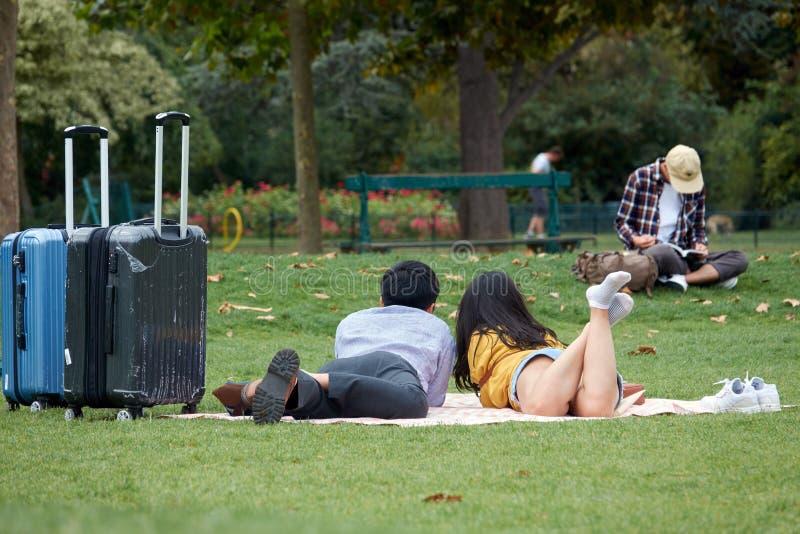La coppia amorosa asiatica dei turisti con le valigie si trova sull'erba verde nel parco Il Champ de Mars a Parigi immagine stock libera da diritti