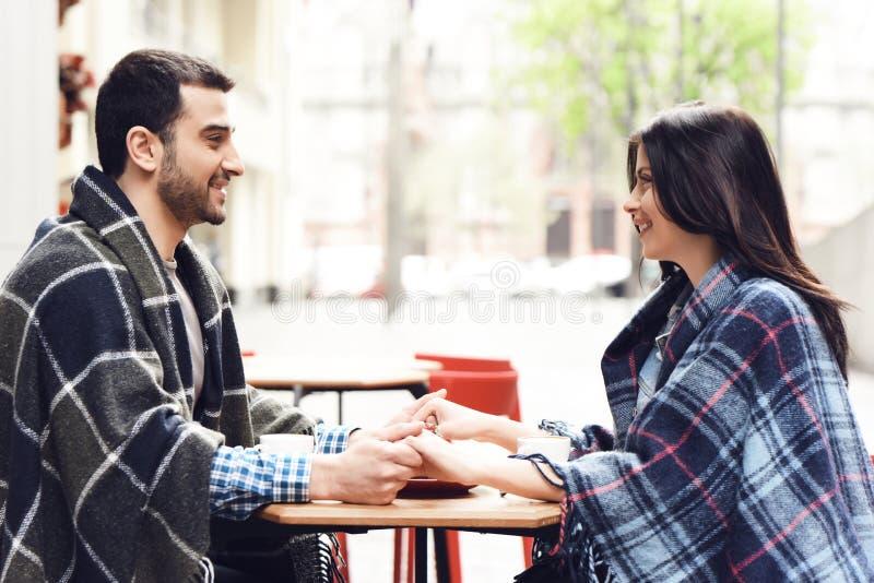 La coppia amorosa in coperte si siede alla tavola fotografia stock