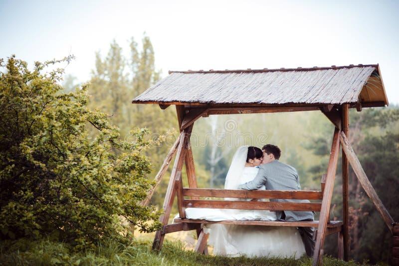 La coppia amorosa di nozze sta sedendosi su un banco immagine stock