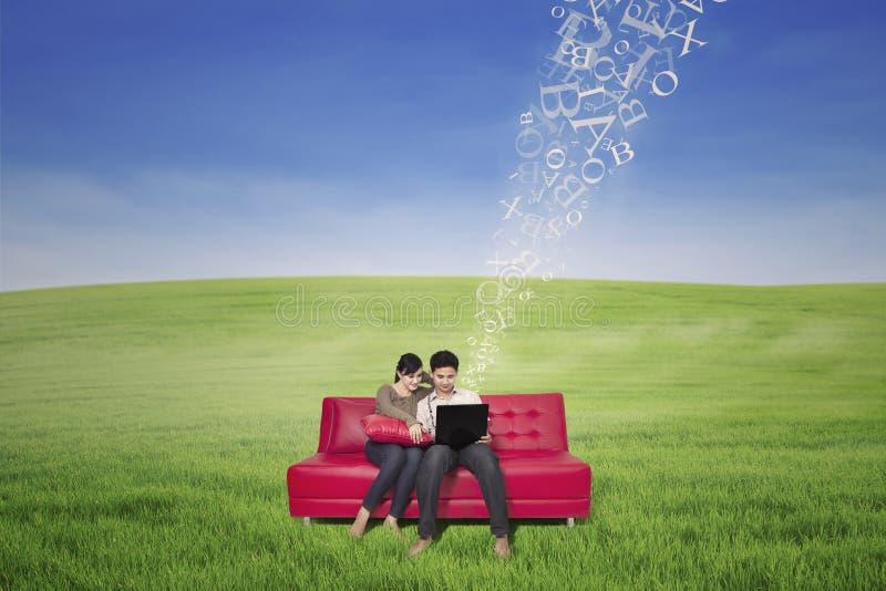 La coppia asiatica facendo uso del computer portatile con il volo segna all'aperto con lettere fotografia stock libera da diritti