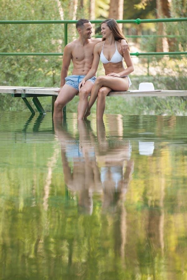 La coppia attiva riposa sulla sponda del fiume un giorno di estate caldo fotografia stock