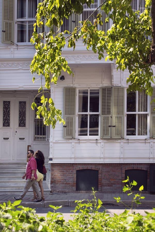La coppia cammina da una casa bianca, di legno, storica fotografia stock