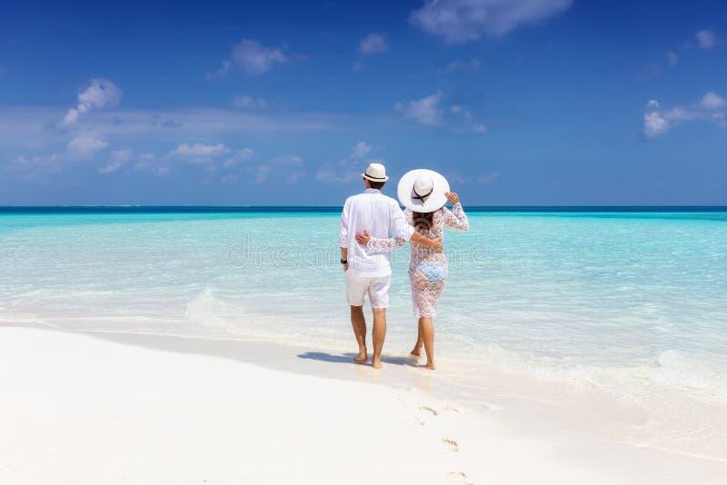 La coppia cammina lungo una spiaggia tropicale in Maldive immagine stock