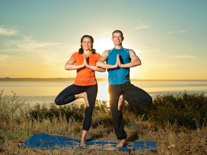 La coppia che fa l'yoga si esercita all'aperto immagine stock