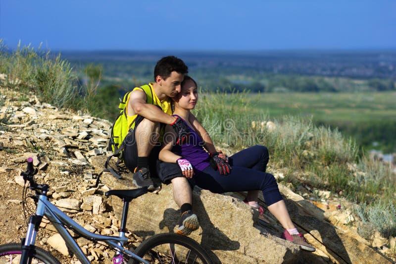 La coppia dei ciclisti sta sedendosi immagine stock