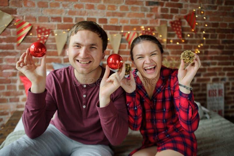 La coppia dei giovani gioca le decorazioni dell'albero di Natale fotografia stock