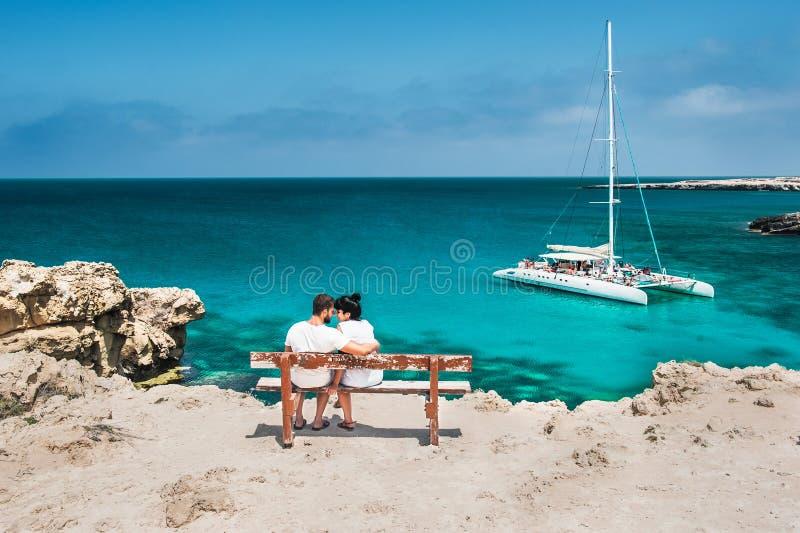 La coppia del viaggiatore di luna di miele che abbraccia su un banco di legno e gode della loro festa tropicale fotografia stock
