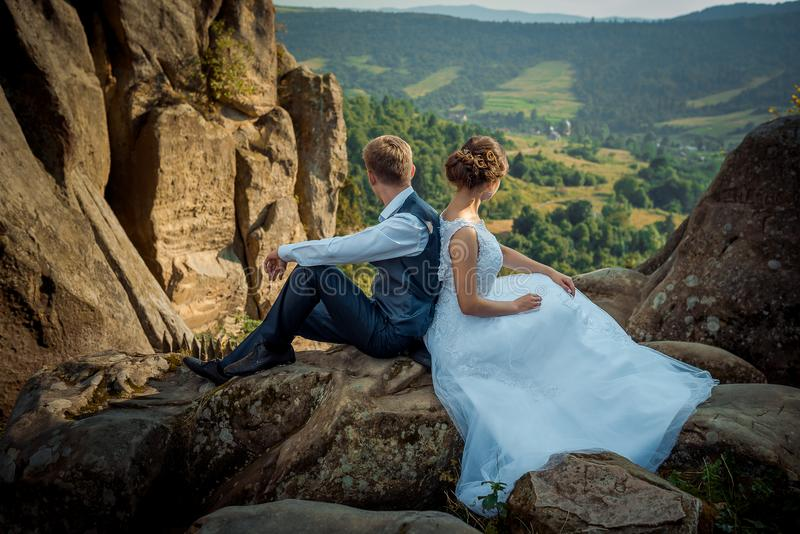 La coppia della persona appena sposata del fascino sta sedendosi sulla roccia contro e sta godendo della vista del paesaggio dura fotografia stock
