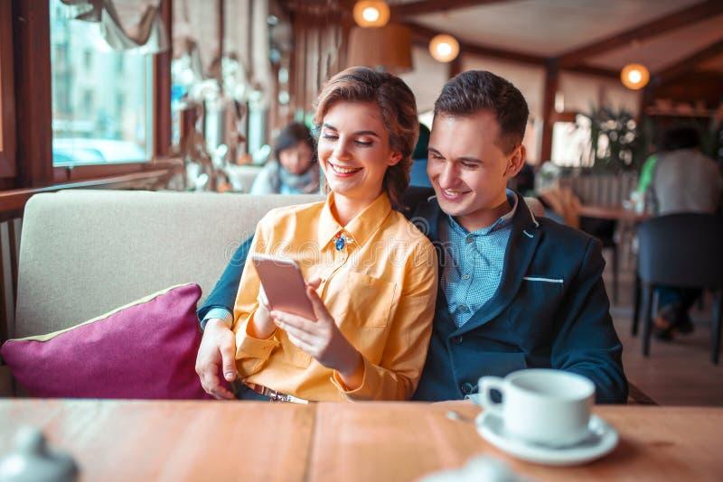La coppia di amore considera l'album di foto del telefono fotografia stock