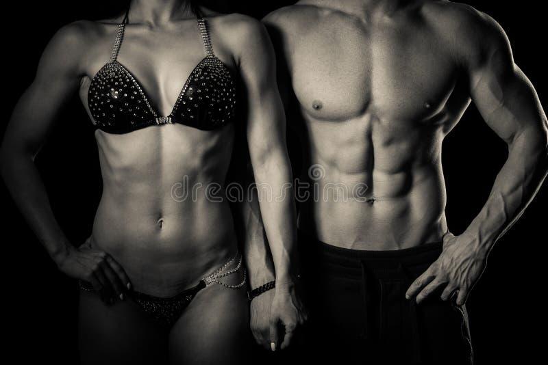 La coppia di forma fisica posa in studio - uomo e donna adatti fotografia stock