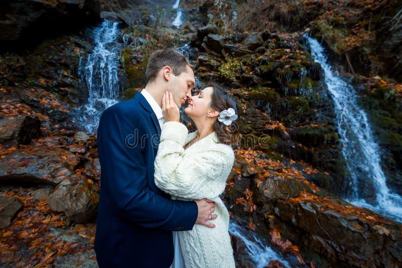 La coppia di nozze abbraccia morbidamente sulla cascata Giorno nebbioso in montagne fotografie stock