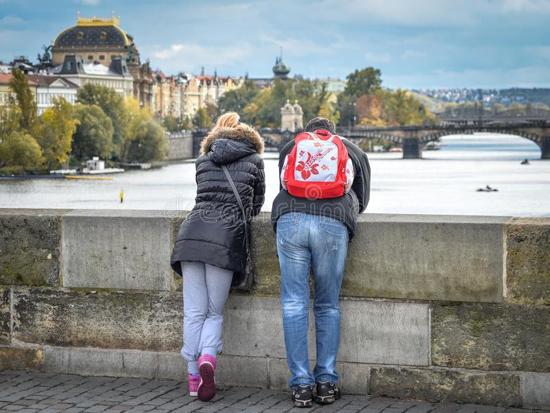 La coppia esamina il fiume ed i ponti della Moldava vicino al centro urbano di Praga, repubblica Ceca di Praga Neolatino a Praga fotografie stock libere da diritti