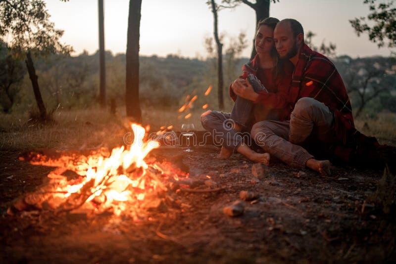 La coppia innamorata si siede sul picnic su fondo della fiamma del falò immagine stock