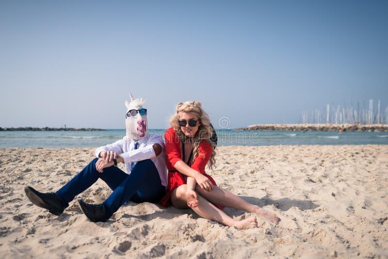 La coppia insolita si siede sulla spiaggia sui precedenti del mare e del cielo immagine stock