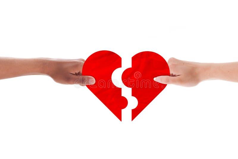 La coppia mista passa il puzzle di forma del cuore della tenuta della tenuta fotografie stock