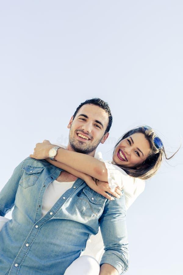 La coppia nell'amore che gode delle loro vacanze estive come l'uomo porta fotografia stock libera da diritti
