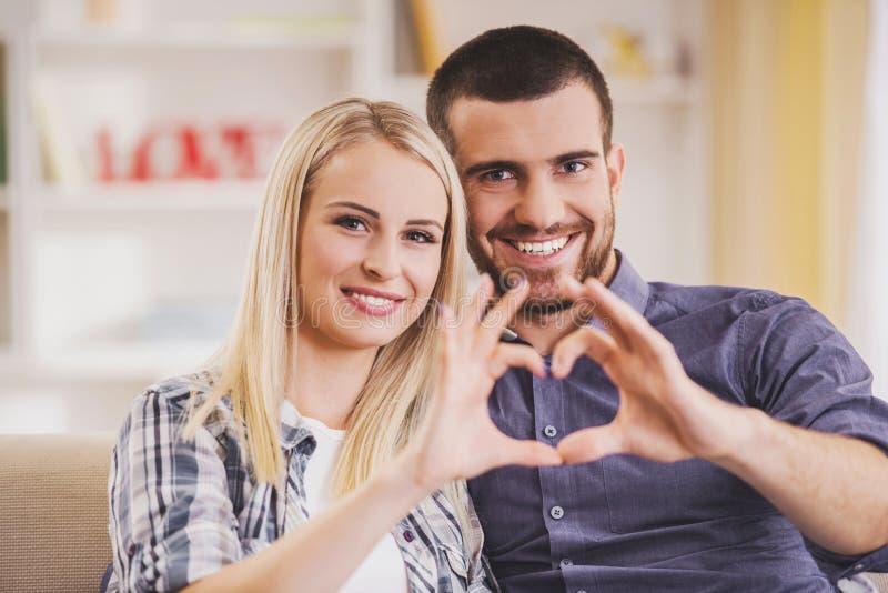 La coppia nell'amore fa il simbolo di cuore con le mani immagine stock